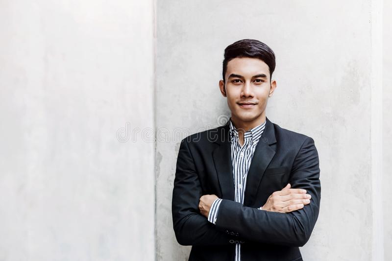 Portrait of Happy Young Businessman standing at the Wall, Smiling and Crossed Arms, Looking at camera stock images