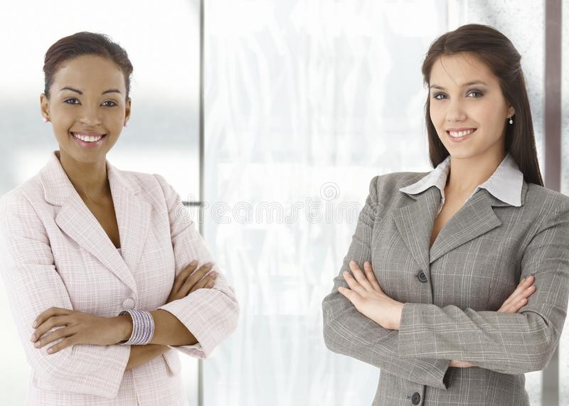 Portrait of happy young businesswomen in office. Portrait of happy young businesswomen standing on office corridor, looking at camera, smiling stock photos