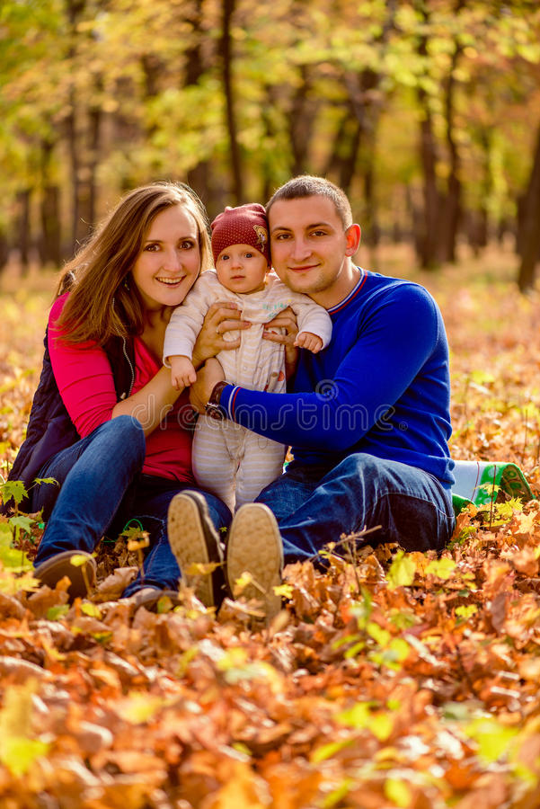 Portrait of a happy young caucasian family holding baby in park. royalty free stock photos