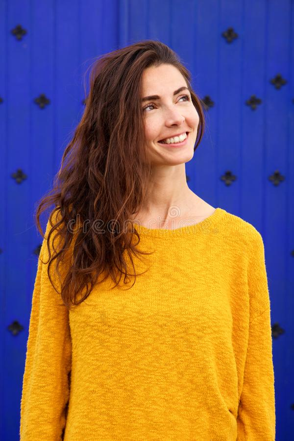 Happy young caucasian woman looking away and smiling against blue background. Portrait of happy young caucasian woman looking away and smiling against blue royalty free stock photo