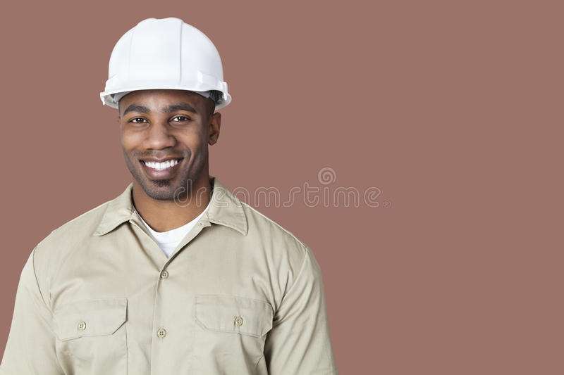 Portrait of happy young construction worker with hardhat over brown background stock images
