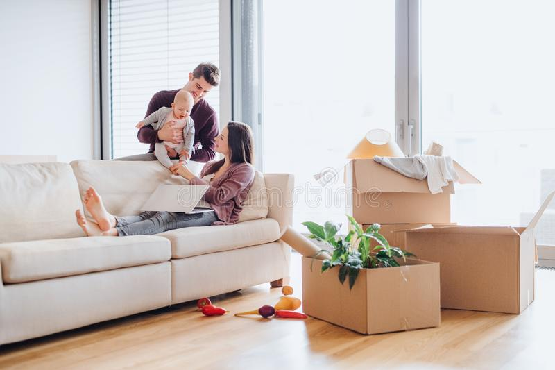 A portrait of young couple with a baby and cardboard boxes moving in a new home. royalty free stock images