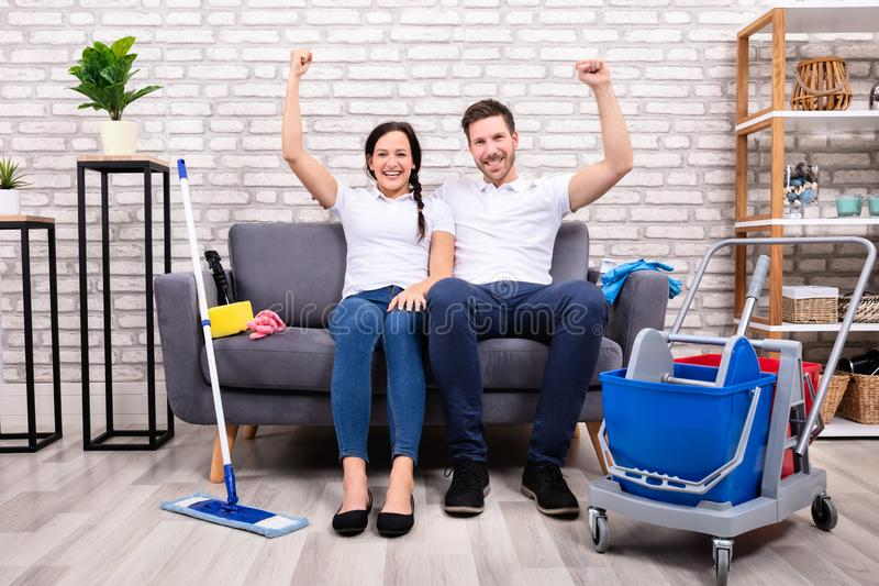 Happy Young Couple With Clenched Fist Sitting On Sofa stock image