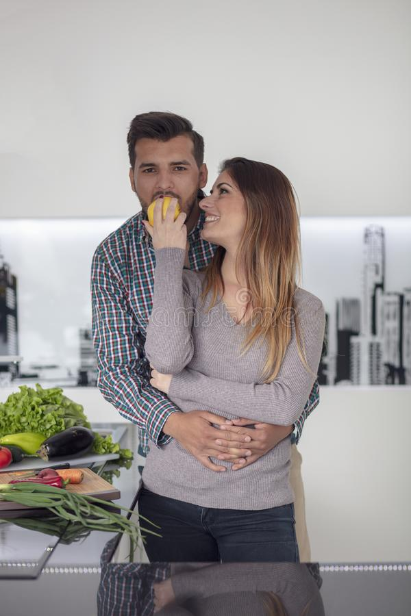 Portrait of happy young couple cooking together in the kitchen at home. royalty free stock image