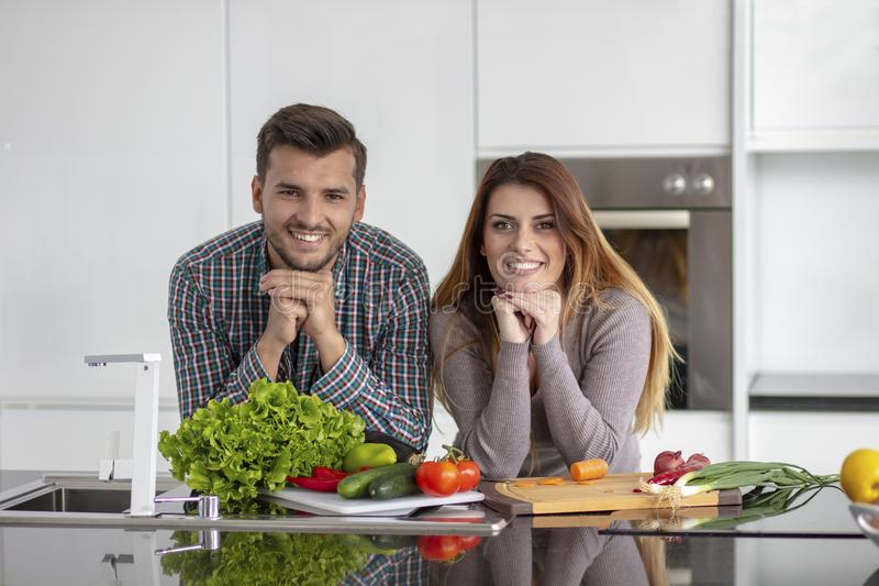 Portrait of happy young couple cooking together in the kitchen at home. royalty free stock images