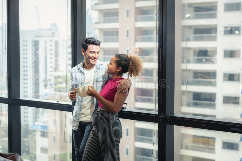 Portrait of Happy Young Couple Love Discussing Something While Holding Coffee Cup in Relaxation Time at Apartment, Relaxing and stock photo