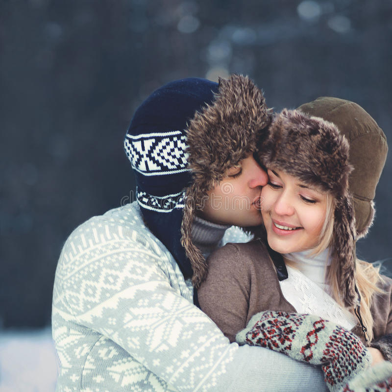 Portrait happy young couple in love at warm winter day, man gentle kissing woman wearing hat and knitted sweater royalty free stock photography