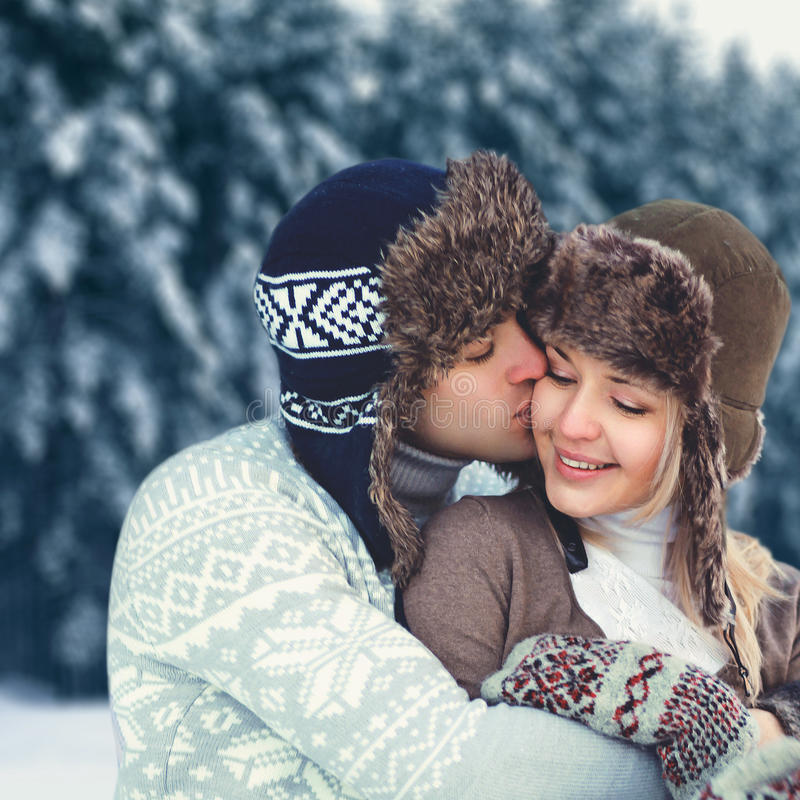 Portrait happy young couple in love at winter day, man gentle kissing woman wearing hat and knitted sweater royalty free stock image