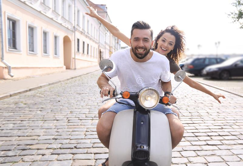 Cheerful young couple riding a scooter and having fun. Portrait of happy young couple on scooter enjoying road trip royalty free stock images