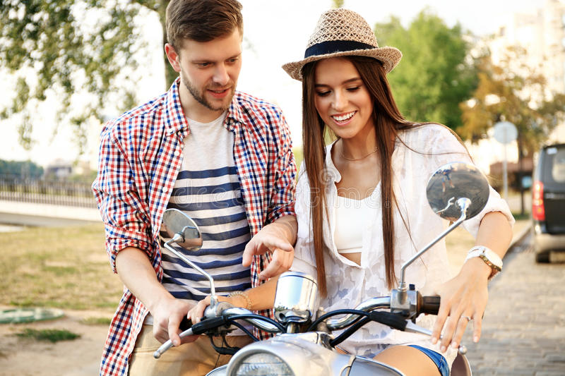 Portrait of happy young couple on scooter enjoying road trip royalty free stock photography
