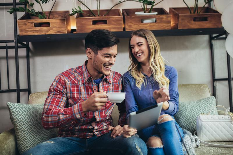 Portrait of happy young couple using a digital tablet together at coffee shop stock photo