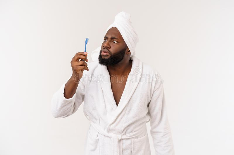 Portrait of a happy young dark-anm brushing his teeth with black toothpaste on a white background. royalty free stock photos
