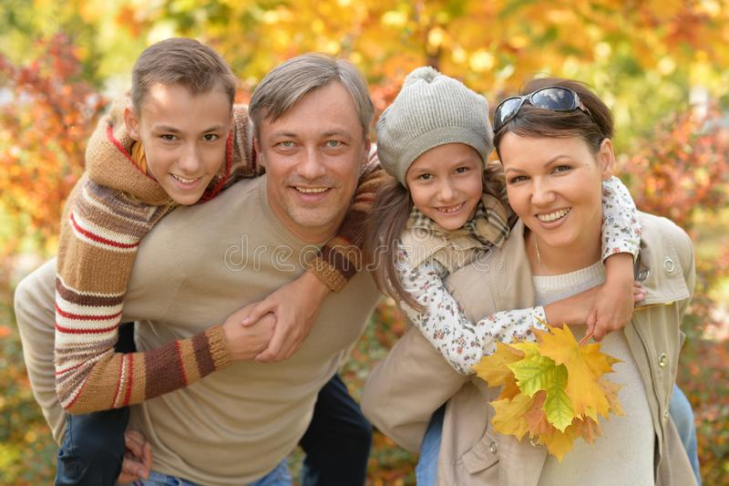 Happy young family resting in autumn park stock images
