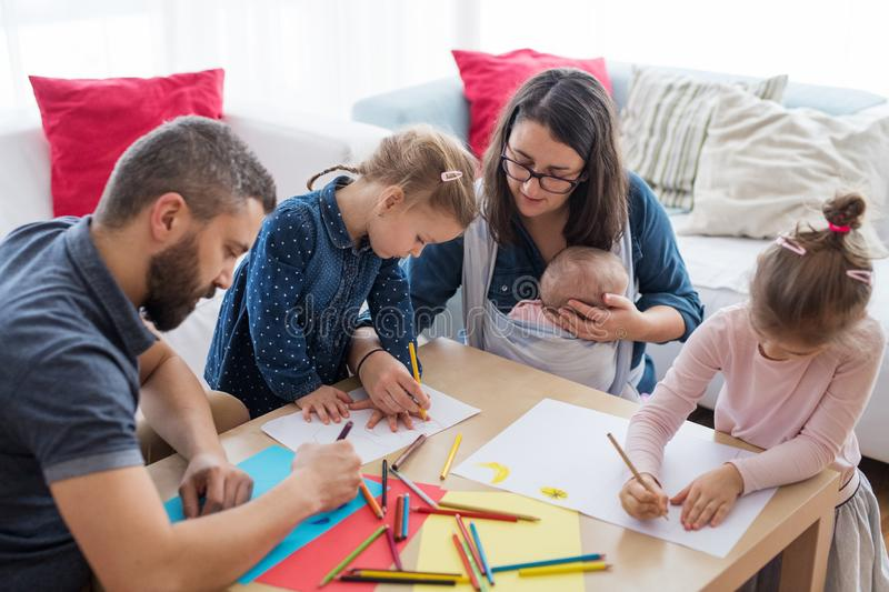 A portrait of young family with small children around table indoors, drawing. royalty free stock image