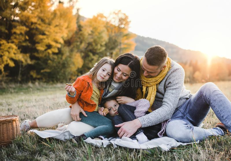 A portrait of young family with two small children in autumn nature at sunset. stock photography