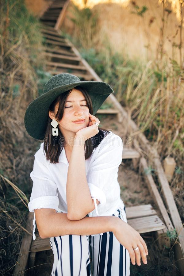 Portrait of happy young fashionable woman relaxing on tropical island. Stylish boho girl in hat sitting on wooden stairs at sandy. Cliff near sea. Summer stock photos