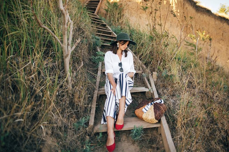 Portrait of happy young fashionable woman relaxing on tropical island. Stylish boho girl in hat sitting on wooden stairs at sandy. Cliff near sea. Summer stock photography