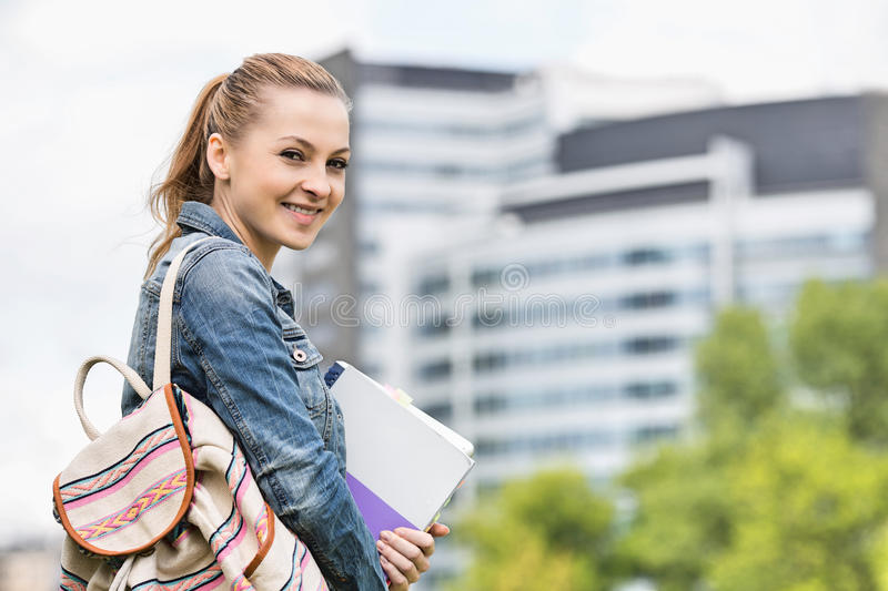 Portrait of happy young female student at college campus stock photo