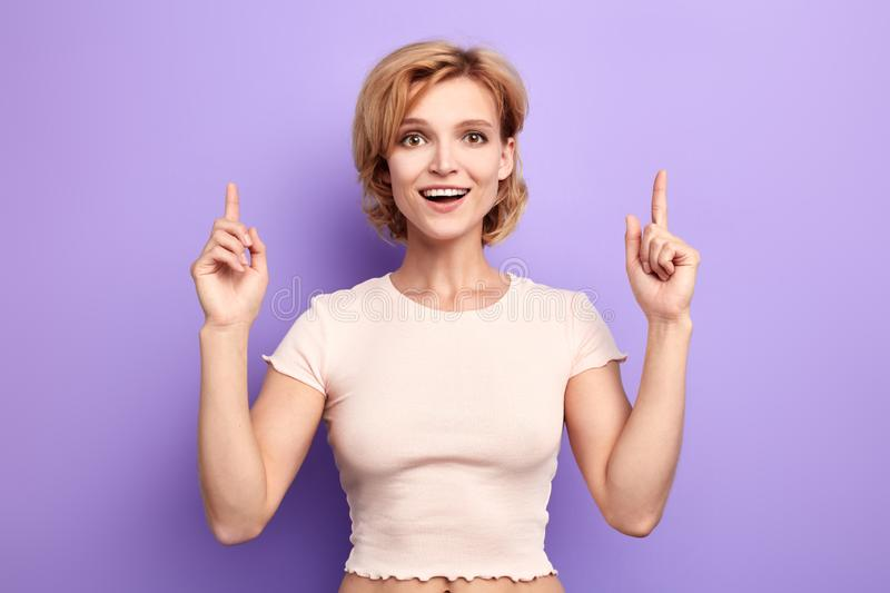 Portrait of a happy young girl dressed casually pointing fingers up royalty free stock photo
