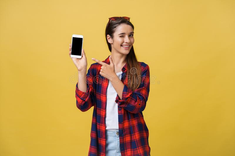 Portrait of a happy young girl dressed in summer pointing finger at blank screen mobile phone isolated over yellow royalty free stock photos