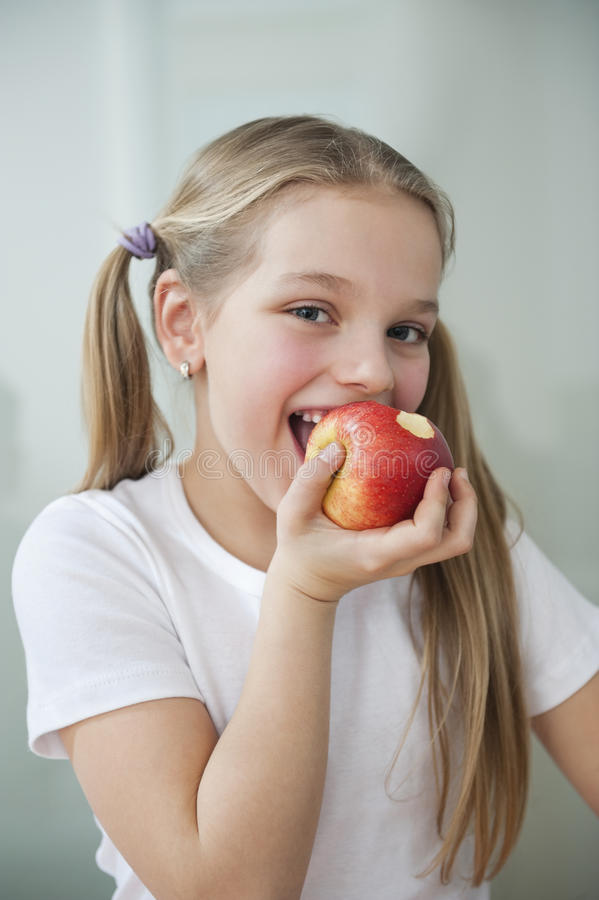 Portrait of happy young girl eating an apple over gray background stock photo