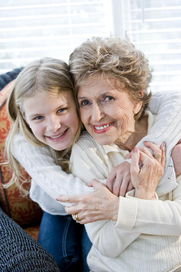 Portrait of happy young girl hugging grandmother. At home stock photos