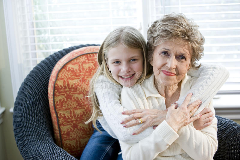 Portrait of happy young girl hugging grandmother. At home royalty free stock photo