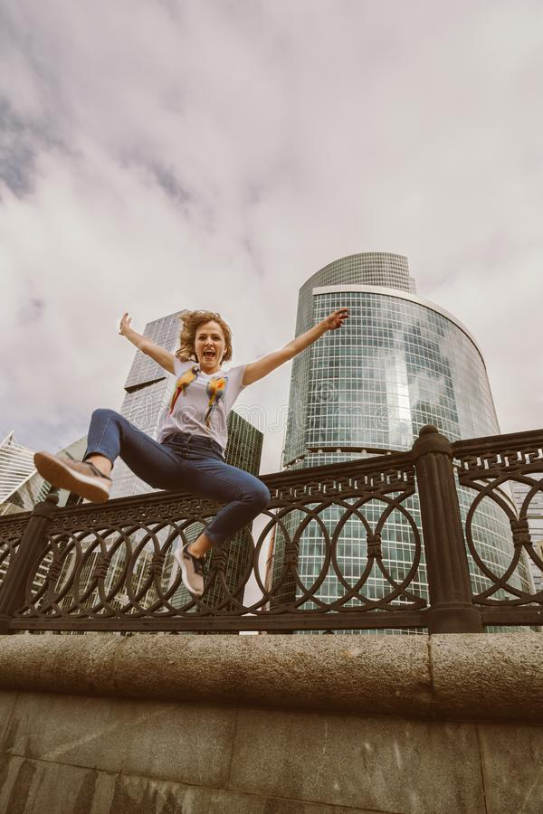 portrait of happy young hipster female jumping up on parapet royalty free stock images