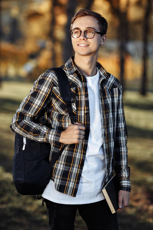 Portrait of happy young male student with glasses in casual outfit holding backpack and posing at the park stock photo