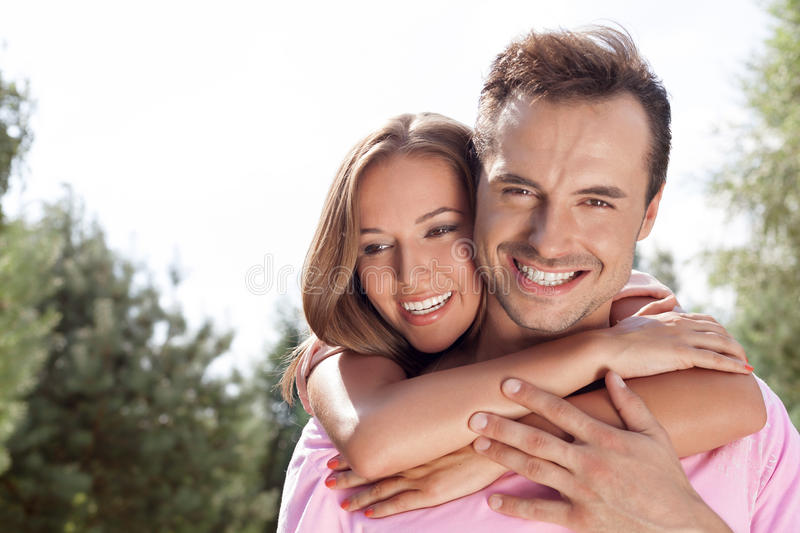 Portrait of happy young man being embrace by woman from behind in park. Portrait of happy young men being embrace by women from behind in park royalty free stock photos