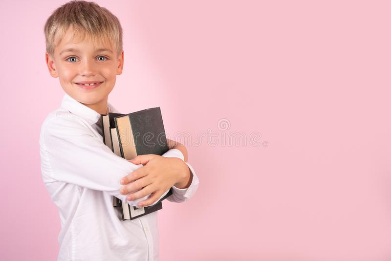 Profile portrait of happy young man holding books in his hands. Back to school. while standing against pink background. place for stock image