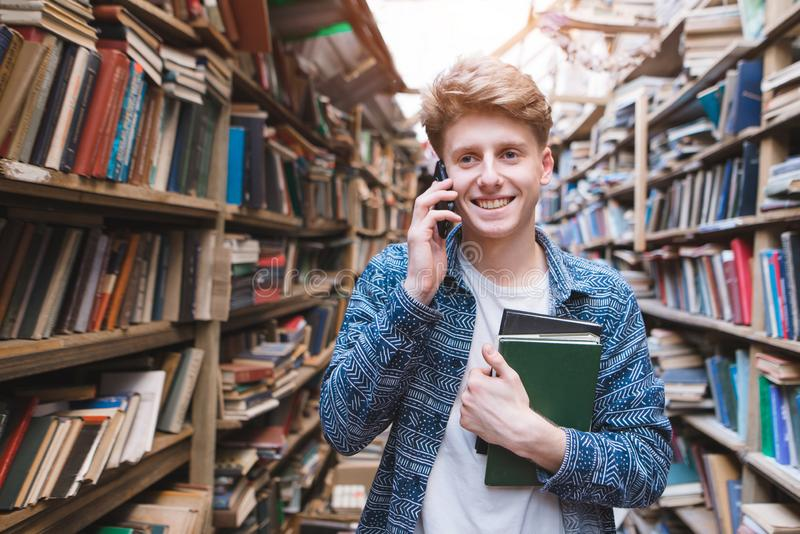 Portrait of a happy young man standing with books in his hands in a public library and talking on the phone royalty free stock image