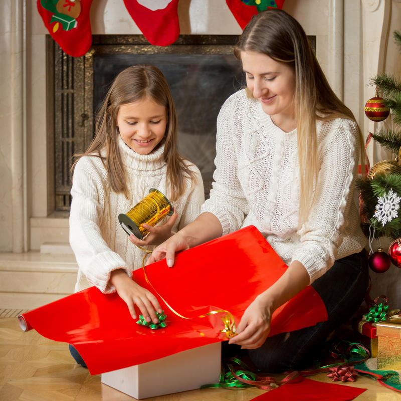 Portrait of happy young mother and daughter packing Christmas gi stock photography