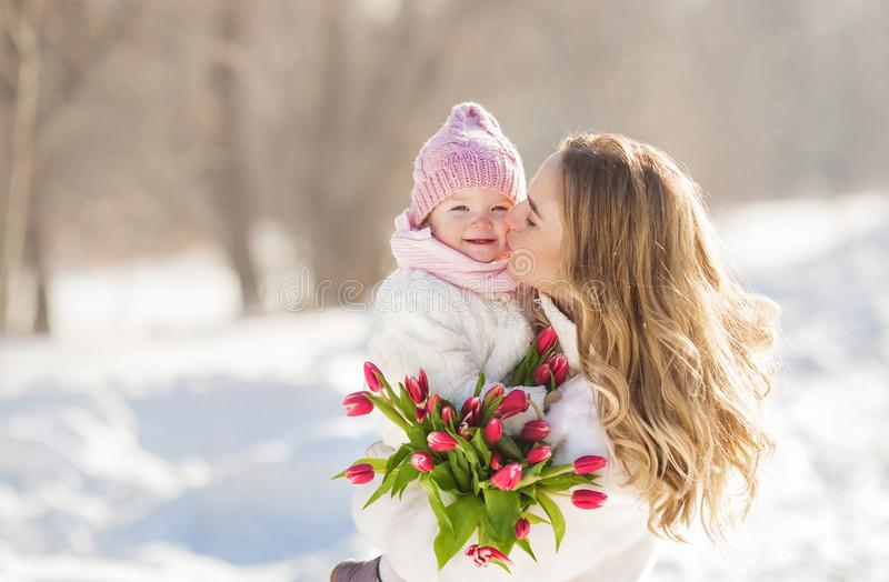 Portrait of happy young mother kisses her baby in the winter sunny day royalty free stock photos