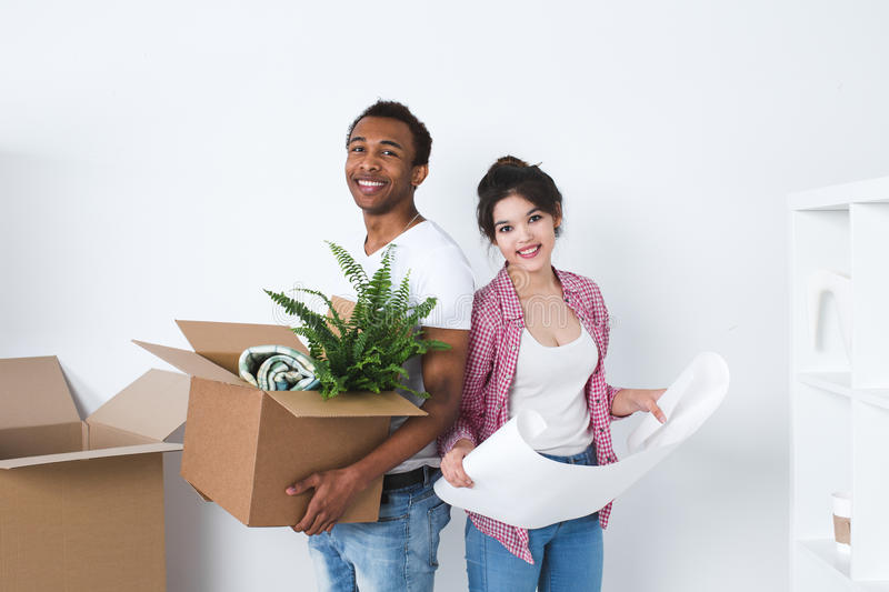 Portrait of happy young multiracial couple in the new home. Dreaming new home and furnishing stock images