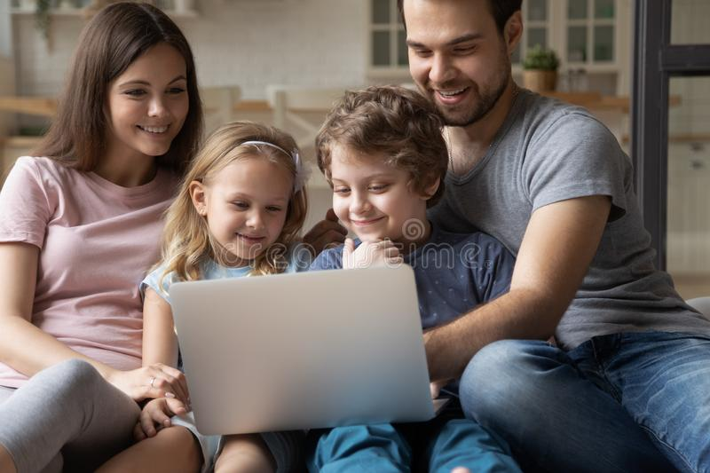Happy young parents sitting with cute little kids, using computer. royalty free stock photo