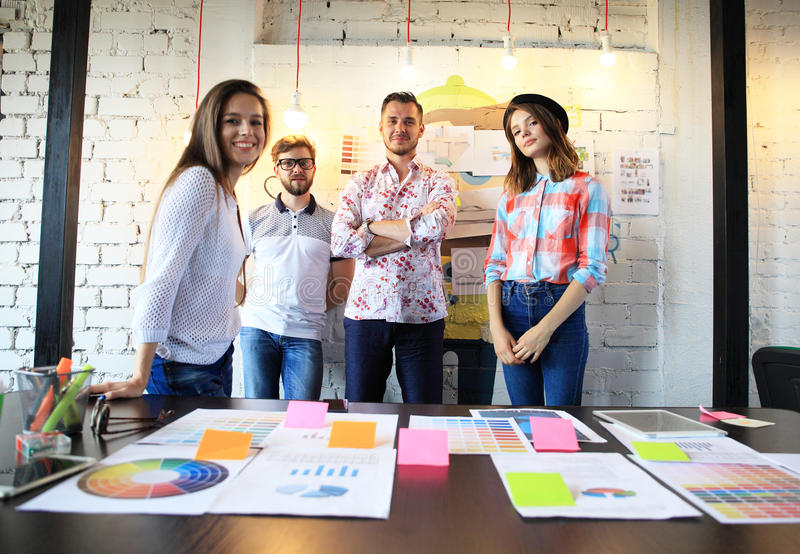 Portrait of happy young people in a meeting looking at camera and smiling. Young designers working together on a stock image
