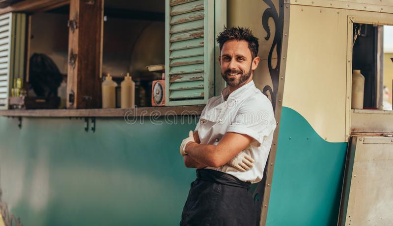 Proud food truck owner. Portrait of happy young salesman standing by his food truck. Proud food truck owner standing with his arms crossed and looking at camera stock photography