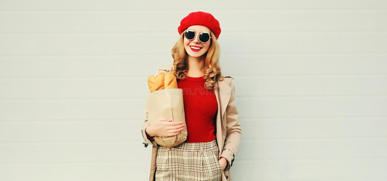 Portrait happy young smiling woman holding grocery shopping paper bag with long white bread baguette on blank gray wall stock photo