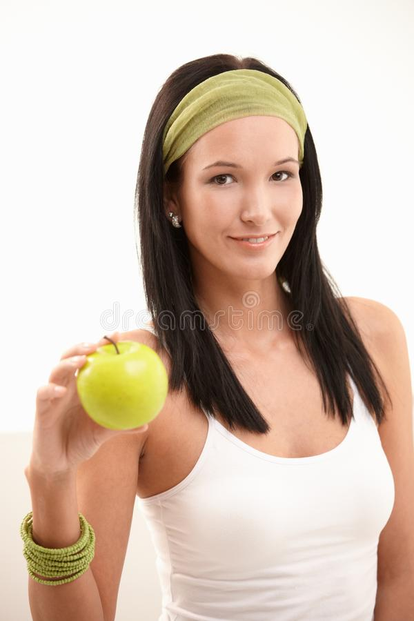 Portrait of happy young woman with apple