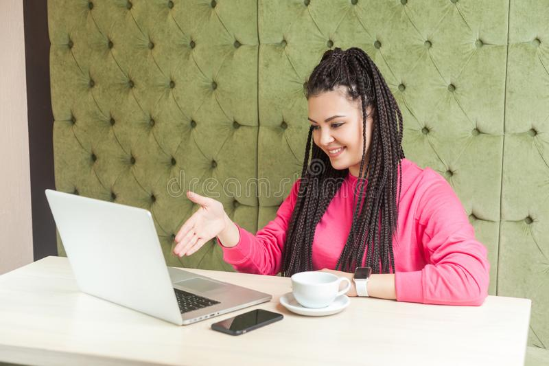 Portrait of happy young woman with black dreadlocks hairstyle in pink blouse sitting in and talking to webcamera at laptop and royalty free stock photography