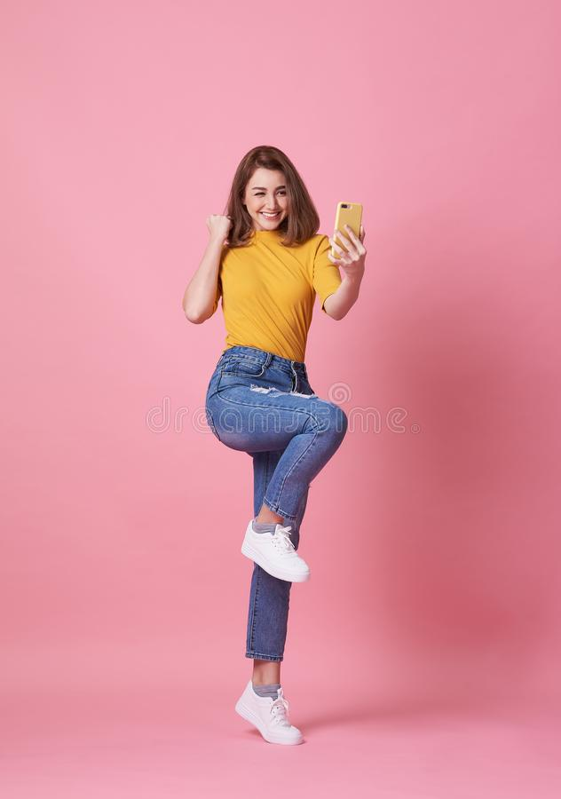 Portrait of a happy young woman celebrating with mobile phone  over pink background stock image