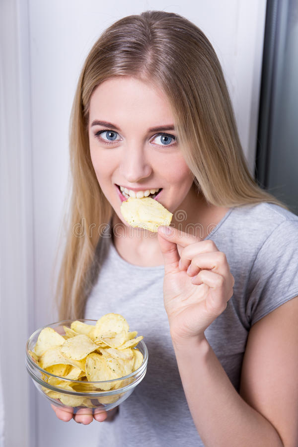 Portrait of happy young woman eating chips stock photos