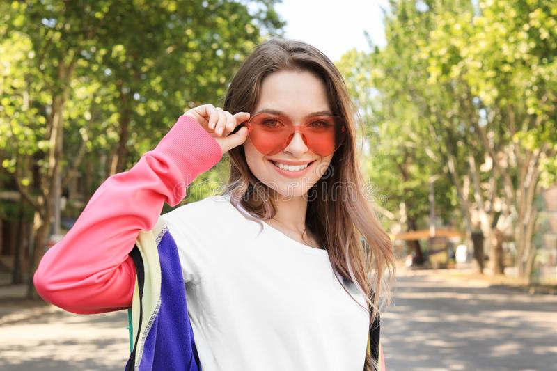 Portrait of happy young woman with heart shaped glasses in spring park. Space for text stock photography