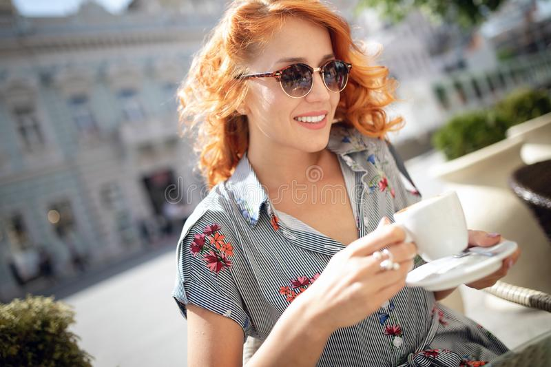 Portrait of happy young woman holding coffee in cafe outdoor stock photography