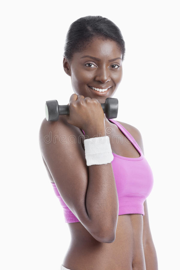 Portrait of happy young woman holding dumbbell over white background royalty free stock images