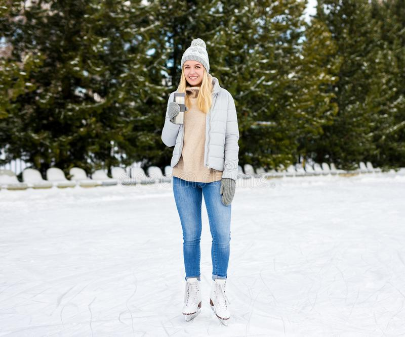 Portrait of happy young woman ice skating and drinking coffee at rink. In winter park stock photo