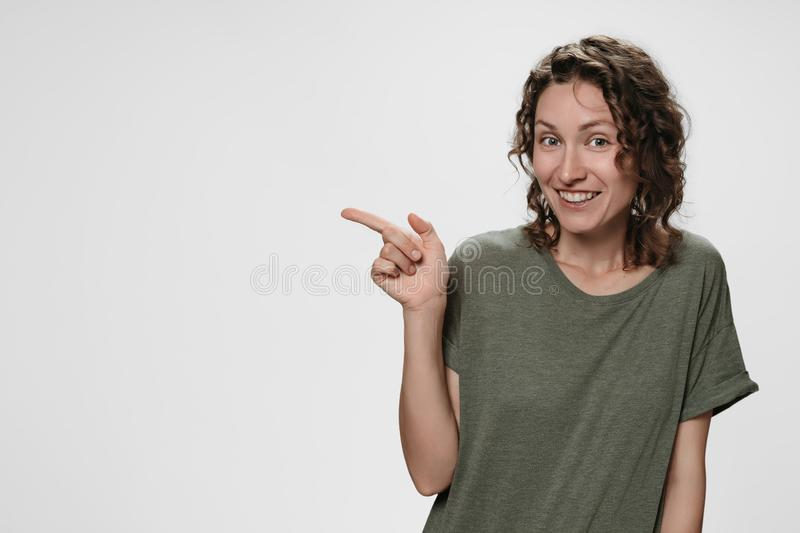 Portrait of happy young woman indicates with index finger at blank copy space. Cheerful woman indicates with index finger at blank copy space, shows place for royalty free stock photos