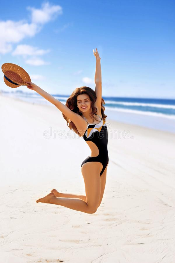 Portrait of happy young woman jumping while enjoying on beach. Woman Applying Sun Cream Creme Sun Protection.Sun Cream. Skin and Body Care. Sunscreen to Her royalty free stock image