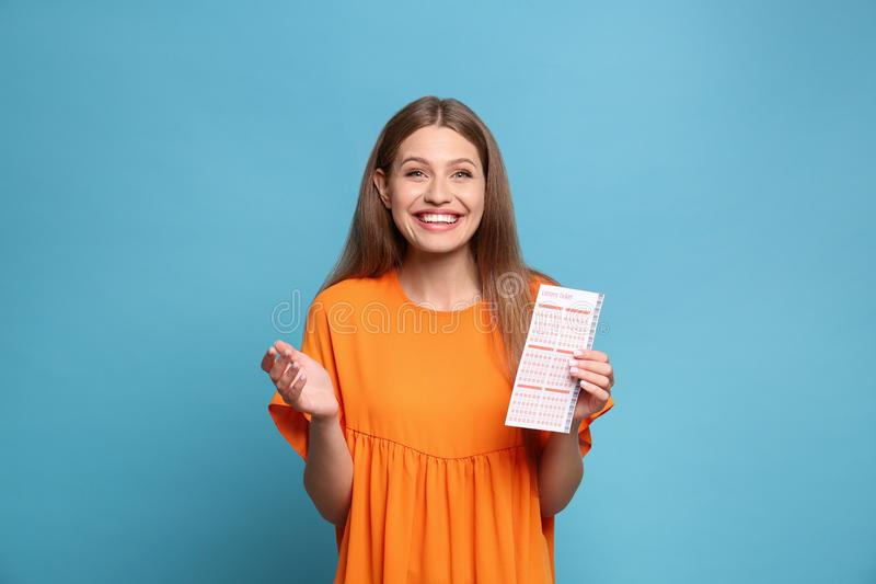 Portrait of happy young woman with lottery ticket on blue background stock images